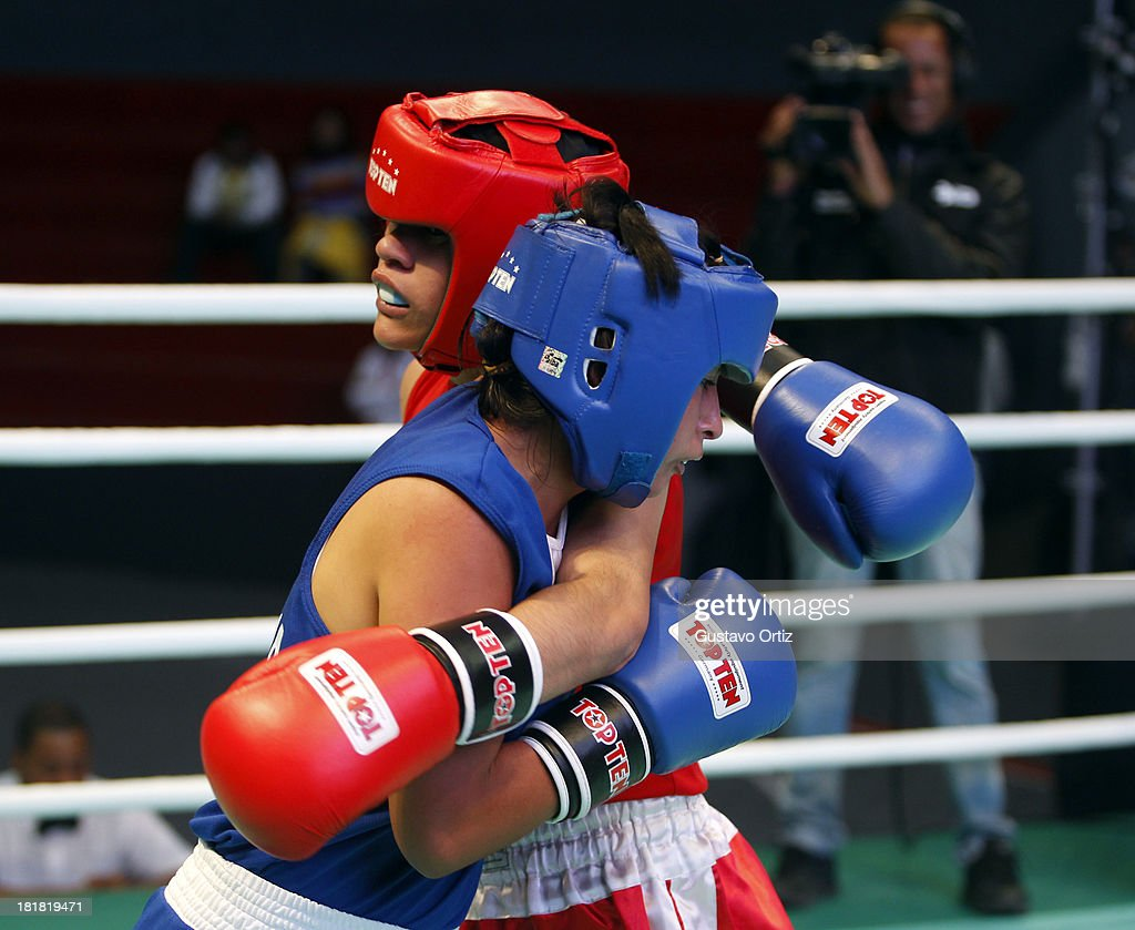 Ayelen Espinosa of Argentina (red) fights with Jessica Centeno of Ecuador (blue) during the Women's 51kg Boxing Final Combat as part of the I ODESUR South American Youth Games at Coliseo Miguel Grau on September 25, 2013 in Lima, Peru.