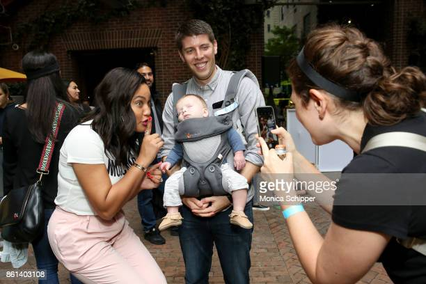 Ayesha Curry poses with a guests sleeping baby during Family Ice Cream Fundae hosted by Mario Batali and Ayesha Curry at Private Park at Hudson on...