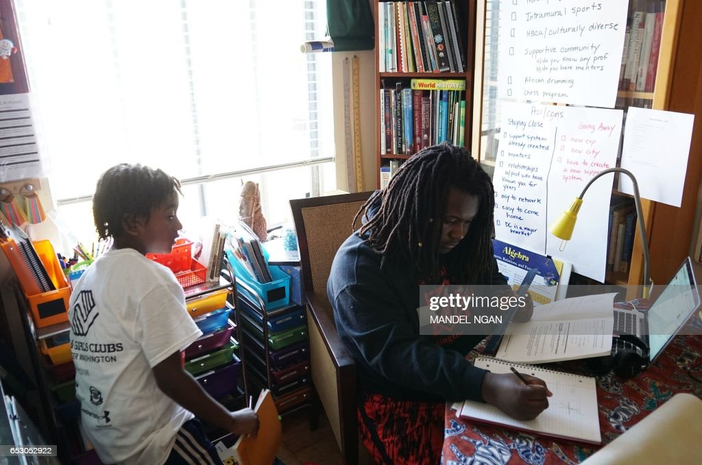 Ayinde (L), 10, and Zion, 17, children of Monica Utsey, 49, do their homework at home in Washington, DC on February 24, 2017. / AFP PHOTO / MANDEL NGAN / With AFP Story by Margaret