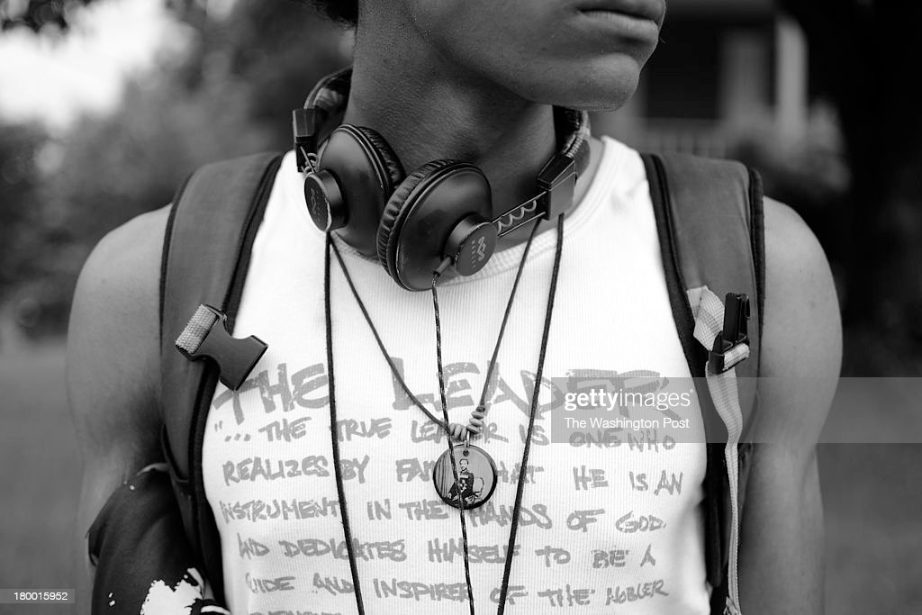 Ayinde Grimes, 17, waits for the bus outside his home in Anacostia in Southeast of Washington, D.C. to take him to his summer internship with the Hissing Black Cat Theater Company, LLC. Ayinde, who is a student at St. Anselm's Abbey High School and a member of the rastafari religion and the DC Youth Poetry Slam Team, always wears his headphones around his neck.