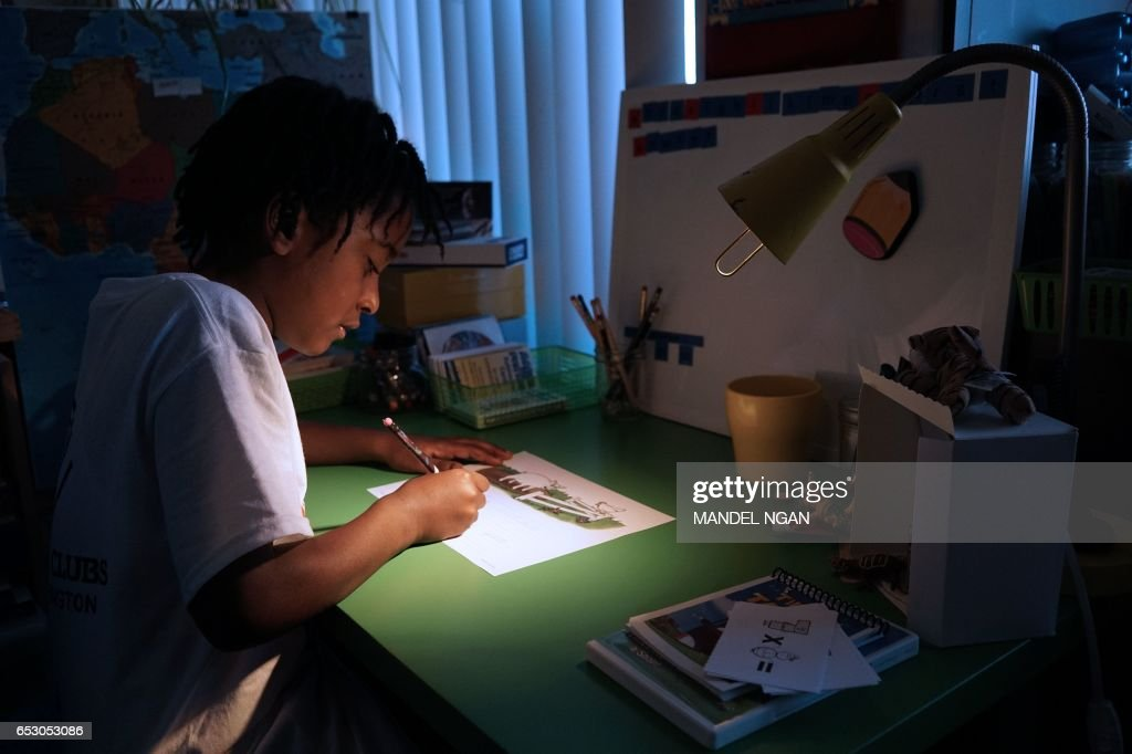 Ayinde, 10, who is homeschooled by his mother Monica Utsey, works at his desk at home in Washington, DC on February 24, 2017. / AFP PHOTO / MANDEL NGAN / With AFP Story by Margaret