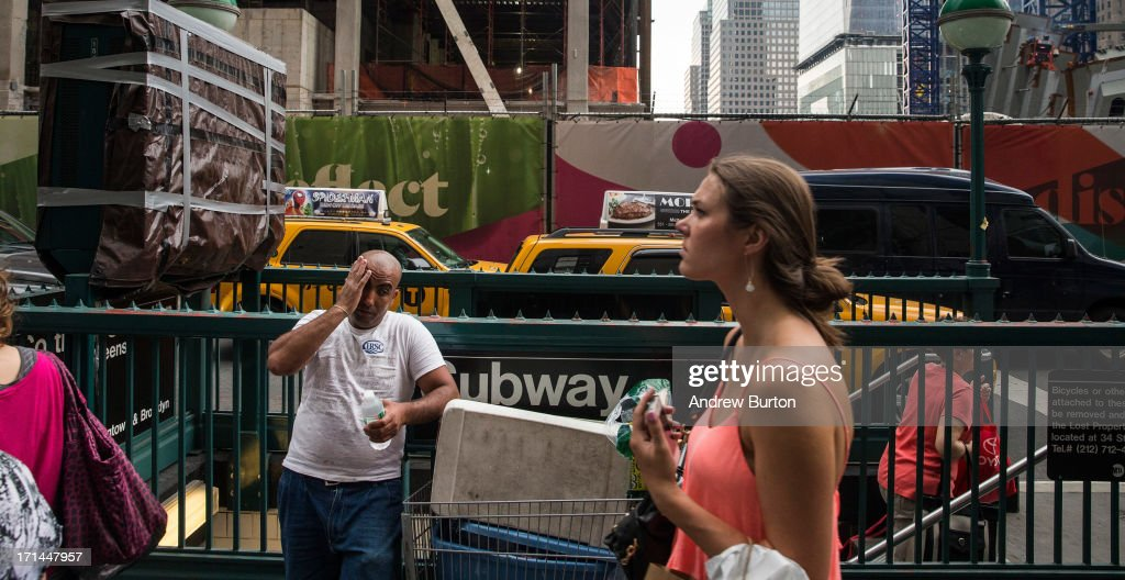 Ayman Grass, originally from Egypt, wipes his brow while selling bottled water near the Ground Zero construction zone on June 24, 2013 in New York City. Construction began on One World Trade Center, the primary building of the new site, on April 27, 2006 and the final piece of the tower was installed on May 10, 2013, making it the tallest building in the Western Hemisphere. Construction is still ongoing on the surrounding complex.