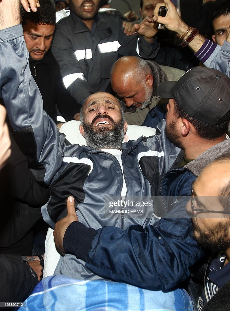 Ayman Sharawna (C), a Palestinian prisoner who was on long-term hunger strike, arrives at al-Shifa hospital in Gaza City on March 17, 2013. Sharawna reached a deal under which he was freed from prison but exiled from the West Bank to the Gaza Strip for 10 years.