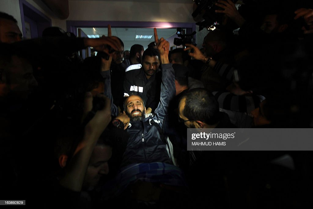 Ayman Sharawna (C), a Palestinian prisoner who was on long-term hunger strike, reacts upon his arrival at al-Shifa hospital in Gaza City on March 17, 2013. Sharawna reached a deal under which he was freed from prison but exiled from the West Bank to the Gaza Strip for 10 years.