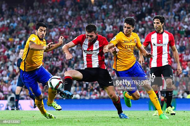 Aymeric Laporte of Athletic Club competes for the ball with Luis Suarez and Marc Bartra of FC Barcelona during the Spanish Super Cup first leg match...