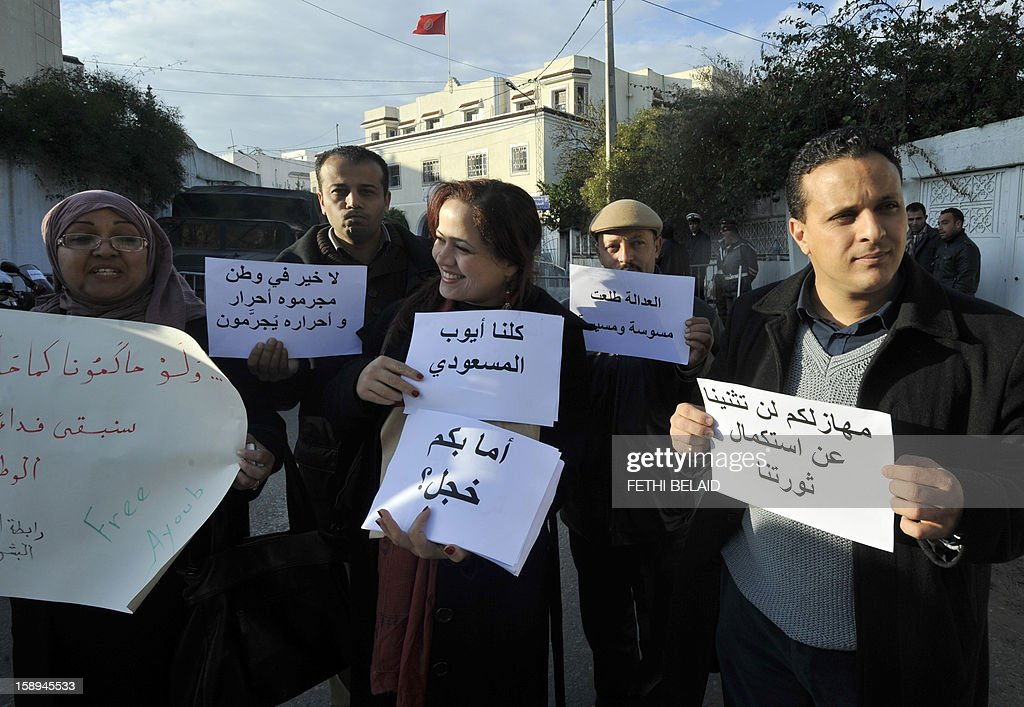 Ayoub Messaoudi (R), former adviser of the Tunisian president, and supporters hold placards as he arrives for his trial on appeal at a military court on January 4, 2013 in Tunis. Messaoudi, former adviser of Moncef Marzouki, was handed a four-month suspended jail term in September 2012 for defaming the army and 'denigrating a military institution'. Arabic writing on sign held by the woman (C) reads: 'We are all Ayoub Messaoudi' and the sign in his hands (R) reads: '...this will not stop us from continuing our revolution.'