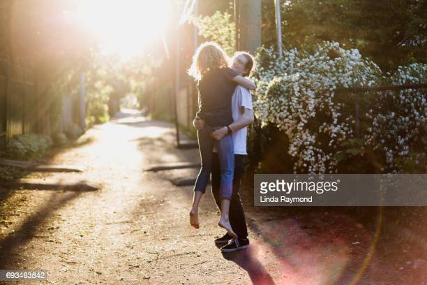 Ayoung boy who takes his girlfriend in his arms in an alley at sunset