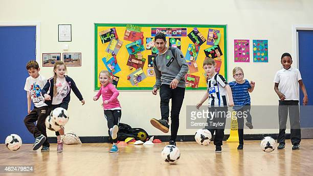 Ayoze Perez and children kick the ball during a Newcastle United Foundation event at The Stocksfield Avenue Primary School on January 29 in Newcastle...