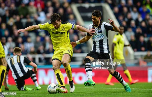 Ayoze Perez of Newcastle United looks to challenge John Mousinho of Burton Albion for the ball during the Sky Bet Championship Match between...