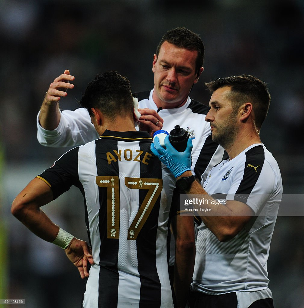 Ayoze Perez of Newcastle United receives medical attention from Newcastle's Physiotherapist Michael Harding and Club Doctor Paul Catterson during the...