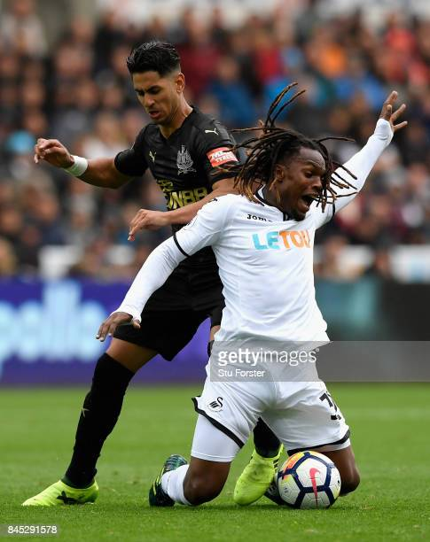 Ayoze Perez of Newcastle United tackles Renato Sanches of Swansea City during the Premier League match between Swansea City and Newcastle United at...