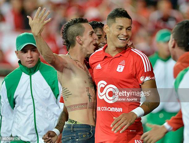 Ayron del Valle of America de Cali celebrates with a fan after scoring the second goal of his team during a match between Deportes Quindio and...