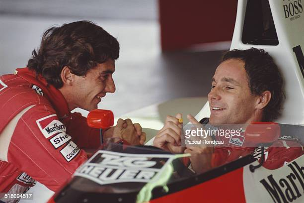 Ayrton Senna driver of the McLarenHonda MP4/5B shares a funny joke with team mate Gerhard Berger during pre season testing 1st February 1990 at the...