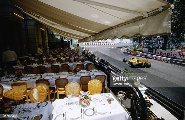 Ayrton Senna drives the Camel Team Lotus Honda Lotus 99Tpast waiters and tables of a restuarant overlooking the circuit during practice for the Grand...