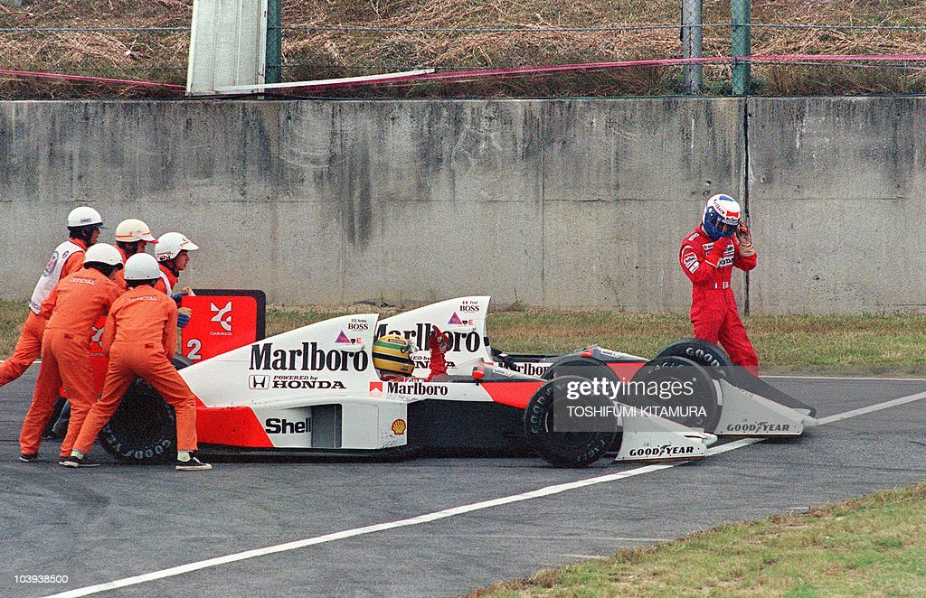 Ayrton Senna of Brazil is given a push from circuit marshals for a restart while his teammate and bitter rival Alain Prost of France leaves his car...