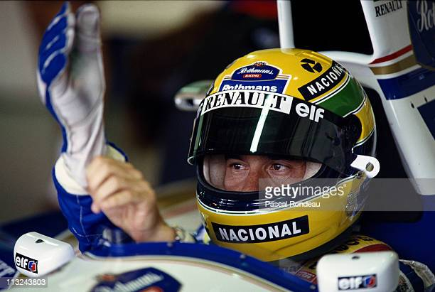 Ayrton Senna pulls on his gloves before he drives the Rothmans Williams Renault Williams FW16 Renault 35 V10 during practice for the Brazilian Grand...