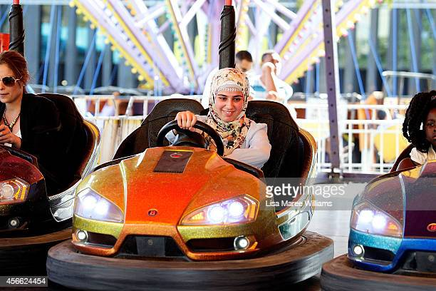 Aysha Kassem rides the dodgem cars during a festival to celebrate Eid alAdha at Paul Keating Park in Bankstown on October 4 2014 in Sydney Australia...
