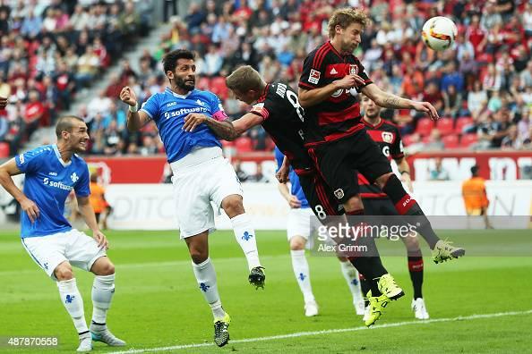 Aytac Sulu of Darmstadt scores his team's first goal against Lars Bender and Stefan Kiessling of Leverkusen during the Bundesliga match between Bayer...
