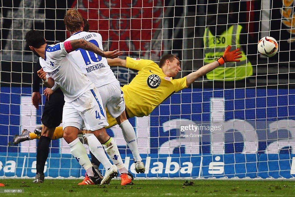 Aytac Sulu of Darmstadt scores his team's first goal against goalkeeper Lukas Hradecky of Frankfurt during the Bundesliga match between Eintracht...
