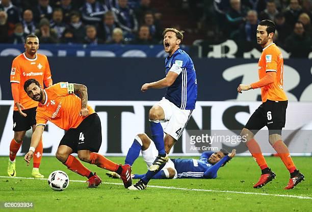 Aytac Sulu of SV Darmstadt 98 challenges Benedikt Hoewedes of Schalke 04 during the Bundesliga match between FC Schalke 04 and SV Darmstadt 98 at...