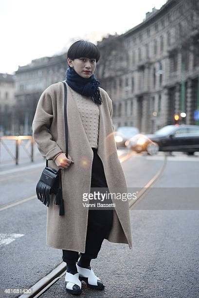 Ayu Ananto poses wearing a Max Mara coat COS pants Proenza Schouler shoes and Acne bag on January 17 2015 in Milan Italy