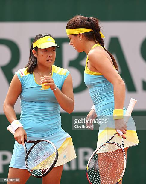 Ayumi Morita of Japan and teammate Sorana Cirstea of Romania talk tactics during their Women's Doubles match against Andrea Hlavackova of Czech...