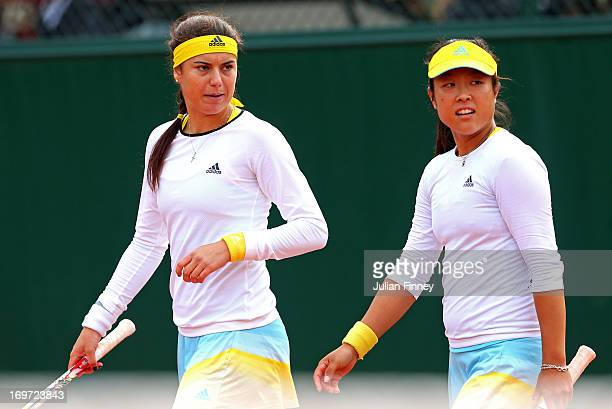 Ayumi Morita of Japan talks with her teammate Sorana Cirstea of Romania during the Women's Doubles match between Simona Halep of Romania and Arantxa...