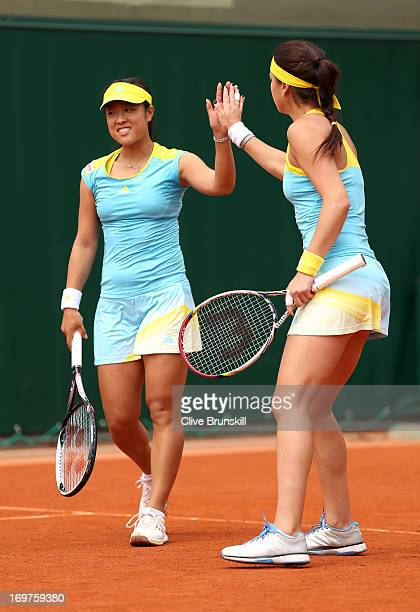 Ayumi Morita of Japan taps hands with teammate Sorana Cirstea of Romania during their Women's Doubles match against Andrea Hlavackova of Czech...