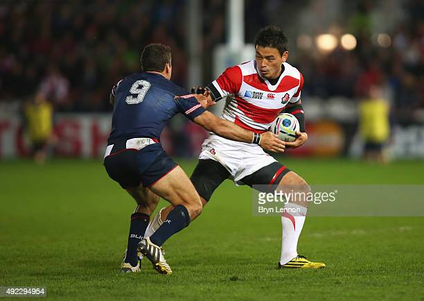 Ayumu Goromaru of Japan hands off Mike Petri of the United States during the 2015 Rugby World Cup Pool B match between USA and Japan at Kingsholm...
