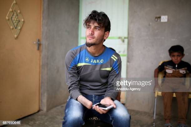 Azad one of the two siblings who was accused of theft and whose right hand was cut off by Daesh plays with a dog in Ninova Iraq on May 23 2017 Azad...
