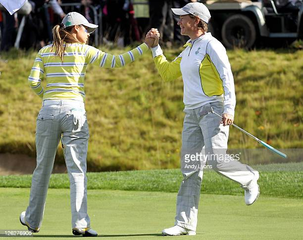 Azahara Munoz of Europe celebrates with Catriona Matthew on the 16th green during the morning foursomes on day two of the 2011 Solheim Cup at Killeen...