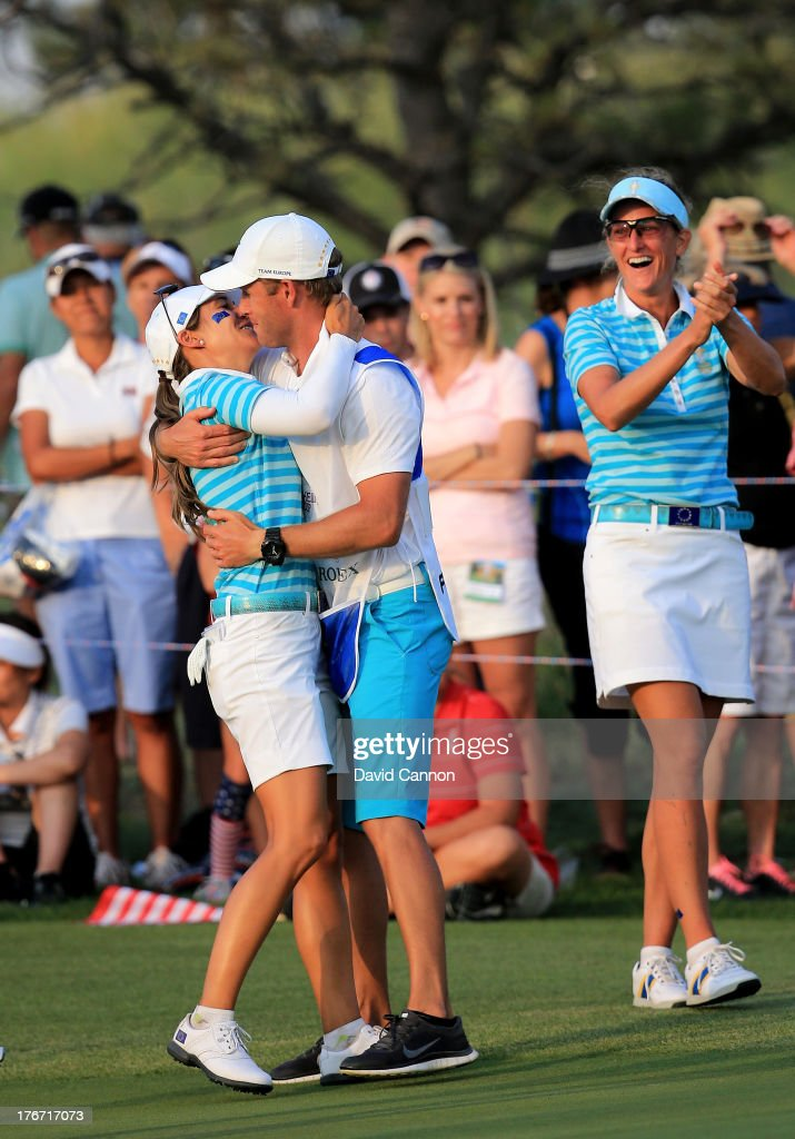 Azahara Munoz of Spain celebrates with her caddie Tim Vickers on the 18th green after her partner Carlota Ciganda had holed a match winning birdie putt against Gerina Piller and Angela Stanford during the afternoon fourball matches for the 2013 Solheim Cup at The Colorado Golf Club on August 17, 2013 in Parker, Colorado.