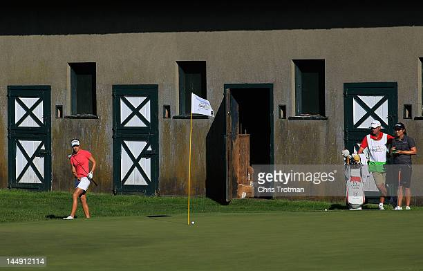 Azahara Munoz of Spain chips on the 16th hole as Candie Kung of Taiwan looks on in the championship match at the Sybase Match Play Championship at...