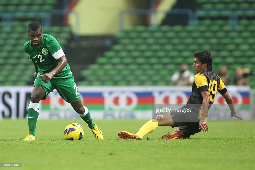Azamuddin Mohd Akil of Malaysia (R) challenges Saudi Arabia's Mansour Alharbi of Saudi Arabia (L) during their football friendly match in Shah Alam Stadium near Kuala Lumpur on March 17, 2013. AFP PHOTO / KAMARUL AKHIR
