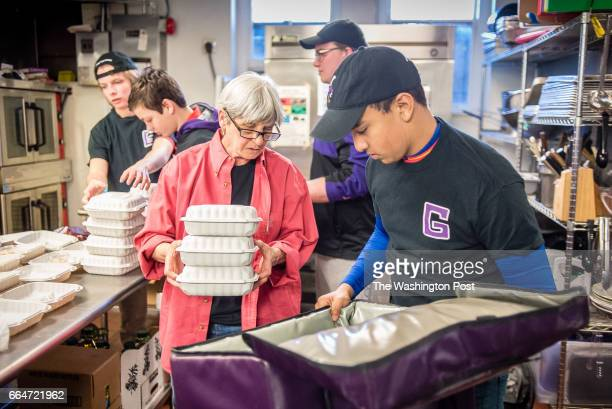 Azariah Sheth holds open a cooler as Patricia Tobin the Campus Kitchen moderator at Gonzaga fills it with boxed lunches Gonzaga High School students...