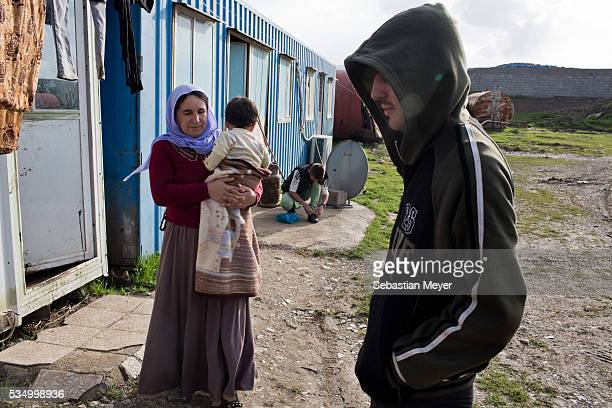 Azdar stands outside the family's house His mother Ghazal holds her grandson Mazal while his brother Serdesht ties his shoes The family of Yezidis...