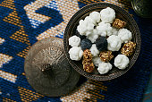 Azerbaijan national candies white nogul in silver bowl, snack for tea. Close-up top view