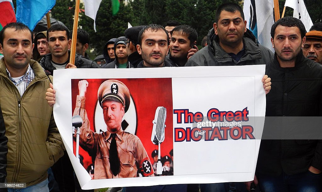 Azerbaijani opposition supporters hold a placard depicting Azerbaijan's President Ilham Aliyev as Charlie Chaplin's dictator during a rally in Baku, on October 27, 2013. Azerbaijani President Ilham Aliyev was sworn in for a third term on October 19, 2013 after romping to victory in a widely criticised election in the oil-rich ex-Soviet country. AFP PHOTO / TOFIK BABAYEV