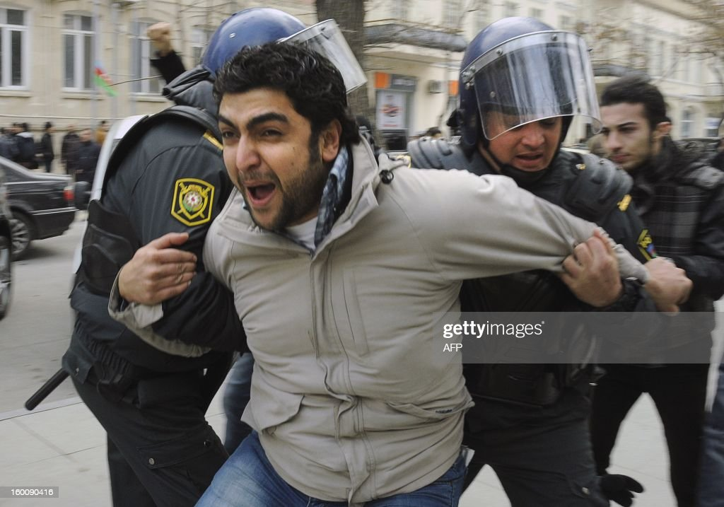 Azeri riot policemen detain protestors in central Baku on January 26, 2013. The police has brutally dispersed an unauthorised rally, beating up and arresting scores of people. Several dozen protesters briefly gathered in Baku's central Sahil square to protest against the police using excessive force against peaceful protests.