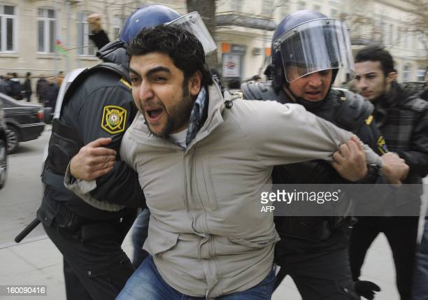 Azeri riot policemen detain protestors in central Baku on January 26 2013 The police has brutally dispersed an unauthorised rally beating up and...