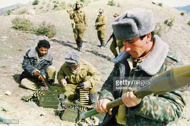 Azeri soldiers feed ammunition belts while another assembles a rocket as they prepare themselves for their next fighting encounter in the village of...