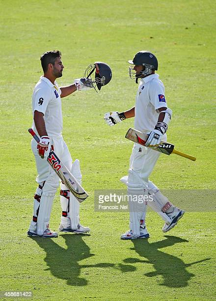 Azhar Ali congratulates Ahmed Shehzad after reaching his century during Day One of the First Test between Pakistan and New Zealand at Sheikh Zayed...