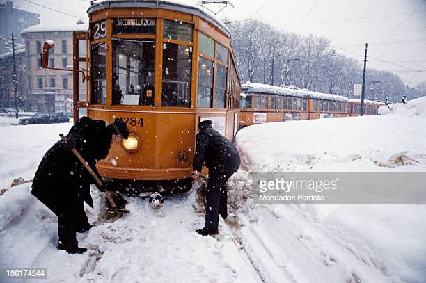 Azienda Trasporti Milanesi workers cleaning the rails from snow to allow the tram traffic One hundred and forty million cubic meters of snow fell in...