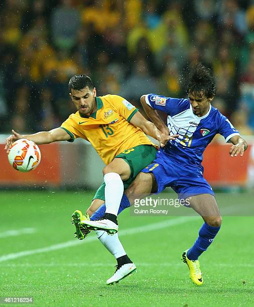 Aziz Behich of Australia is tackled by Ali Almaqseed of Kuwait during the 2015 Asian Cup match between the Australian Socceroos and Kuwait at AAMI...