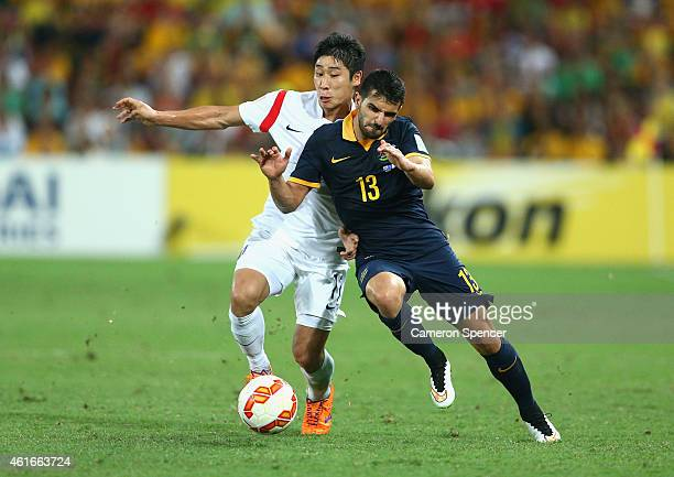 Aziz Behich of the Socceroos is tackled by Lee Keunho of Korea during the 2015 Asian Cup match between Australia and Korea Republic at Suncorp...