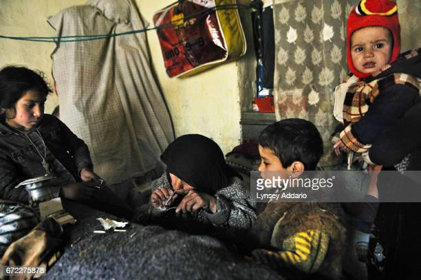 Aziza about 35 smokes opium in her home one last time before leaving for detox at the Sanga Amaj center for women addicts as her children look on in...
