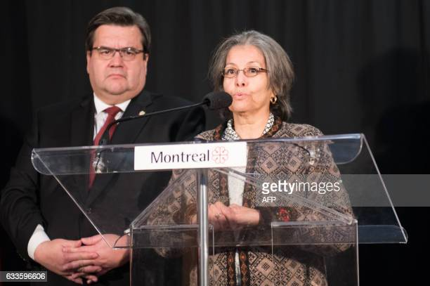 Aziza Blili of the Canadians Muslim Federation speaks as Denis Coderre the mayor of Montreal looks on at the funeral of three of the six victims of...