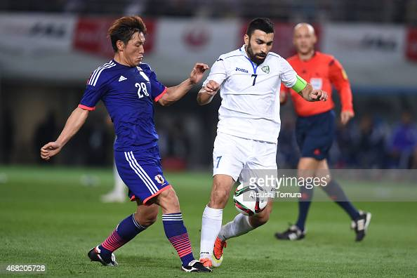 Azizbek Khaydarov of Uzbekistan competes for the ball with Toshihiro Aoyama of Japan during the international friendly match between Japan and...