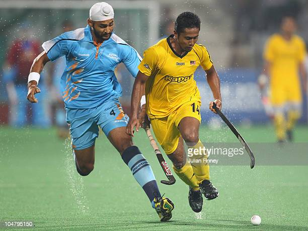Azlan Misron of Malaysia battles with Sandeep Singh of India at Major Dhyan Chand National Stadium during day two of the Delhi 2010 Commonwealth...