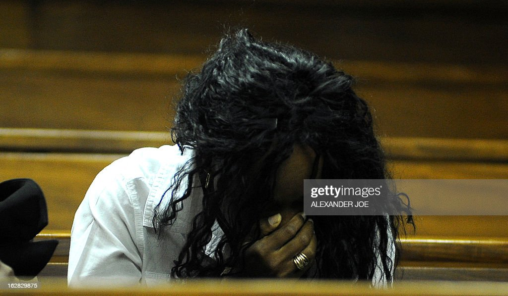 Azuka Okah, wife of Nigerian militant leader Henry Okah, reacts in court after her husband's case was posted because he changed his legal team at Johannesburg High Court on February 28, 2013. Okah is convicted of 13 terrorism charges, including the 2010 independence day bombings in Abuja. Okah was found guilty of masterminding attacks including twin car bombings in Abuja on October 1, 2010, and two explosions in March 2010 in the southern Nigerian city of Warri, a major hub of the oil-rich Delta region. He faces a minimum term of life in prison.